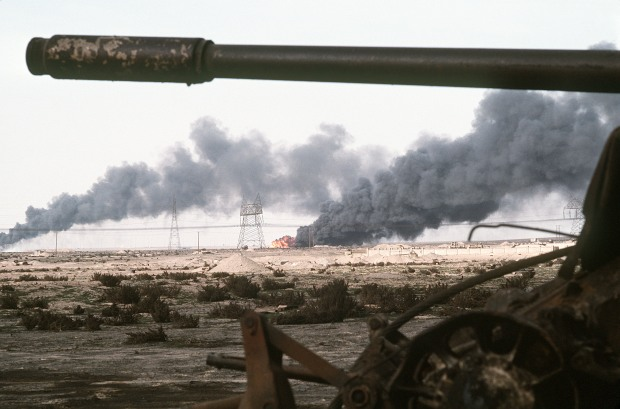 A Kuwaiti oil field set afire by retreating Iraqi troops burns in the distance beyond an abandoned Iraqi tank following Operation Desert Storm.