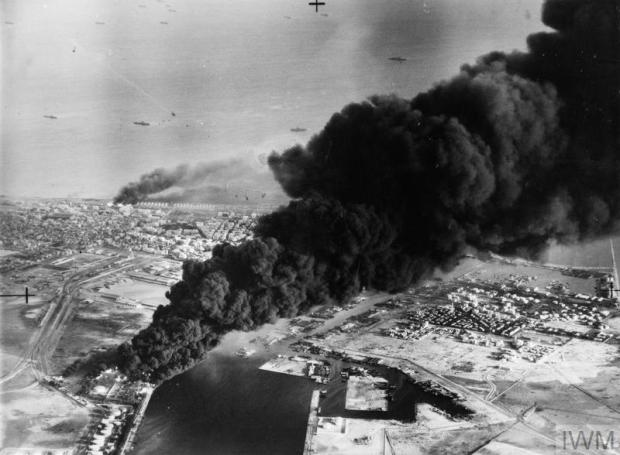 THE SUEZ CRISIS (OPERATION MUSKETEER) 1956 (MH 23509) Smoke rises from oil tanks beside the Suez Canal hit during the initial Anglo-French assault on Port Said, 5 November 1956. Copyright: © IWM. Original Source: http://www.iwm.org.uk/collections/item/object/205022435