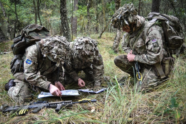 Pictured are members of C Squadron from the Queen's Royal Hussars checking their position on a map during a Junior NCO Cadre.  (Cadre- A small group of people specially trained for a particular purpose or profession)  Queen's Royal Hussars (The Queen's Own and Royal Irish) (QRH) Junior Non Commissioned Officer (JNCO) Cadre course on Sennelager Training Area - members of C Squadron complete section attacks on enemy positions during their JNCO Cadre after spending the last few days learning what it takes to become a Junior NCO.     Based in Sennelager, Germany, the Queen's Royal Hussars (The Queen's Own and Royal Irish) is the senior Armoured Regiment of the British Army with a long history and tradition of excellence.  Equipped with the Challenger 2 Main Battle Tank and the Scimitar reconnaissance vehicle (CVR(T)), we are also trained in a variety of roles, including on other armoured vehicles.